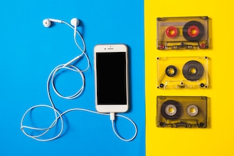 Smartphone connected with earphone and cassette tapes on dual background