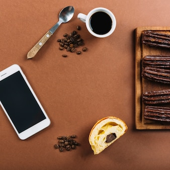 Smartphone, cup of coffee and eclairs