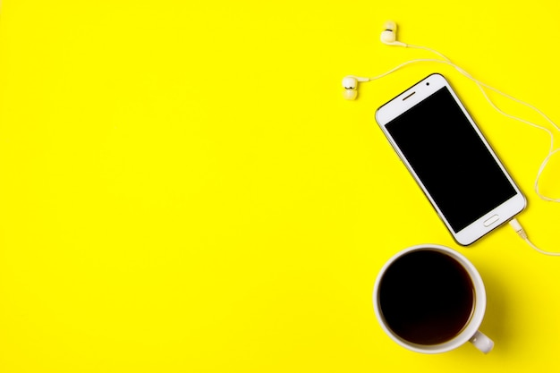 Smartphone and cup of coffee on a yellow background