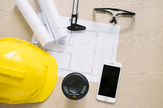 Smartphone and cup near construction supplies