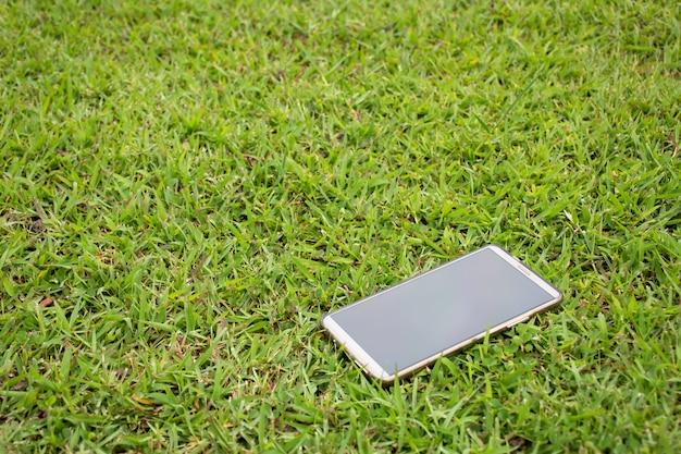 스마트폰은 공공 공원의 푸른 잔디에 떨어집니다.