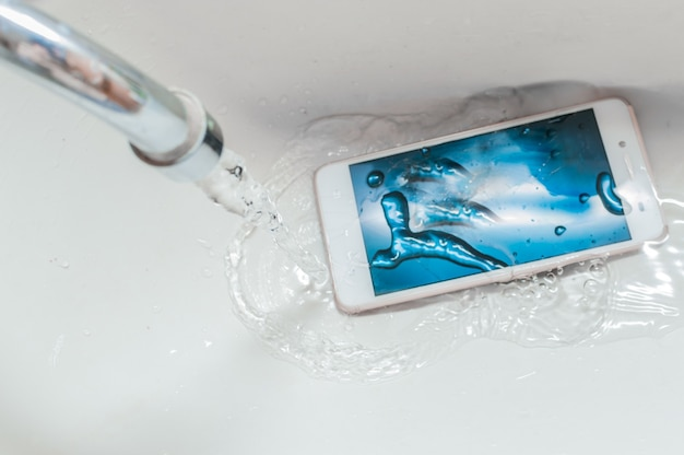 Smartphone dropped into the sink under the water. concept mobile phone repair. recessed phone into the water.