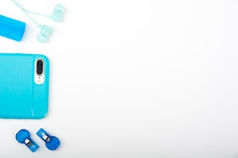 Smartphone; earphone and whistle on white surface