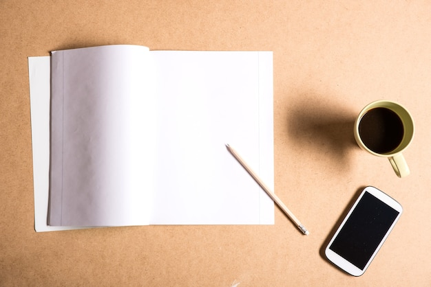 A smartphone and a exercise book on a wooden desk.