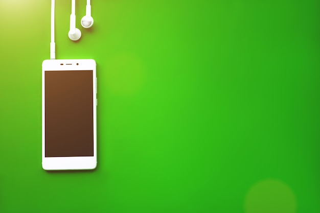 Smartphone flat lay on a green background. music concept. audio, listen.