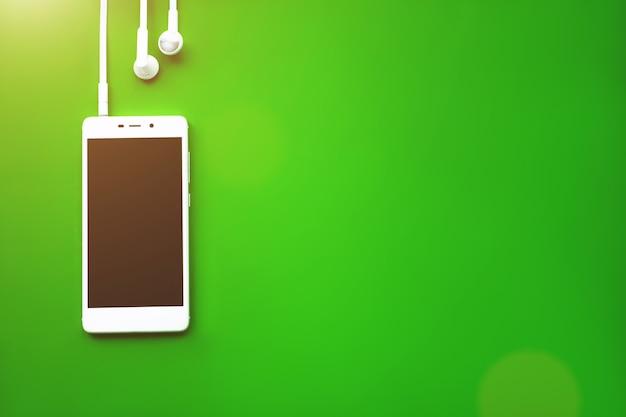 스마트폰은 녹색 배경에 평평하게 놓여 있습니다. 음악 개념입니다. 오디오, 들어보세요.