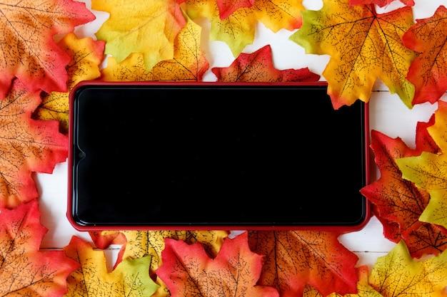 画面上のテキストとカエデの葉の背景のためのスマートフォン。