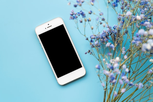 Smartphone and fresh flower twigs