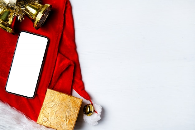 Smartphone, gift and bells on santa claus hat