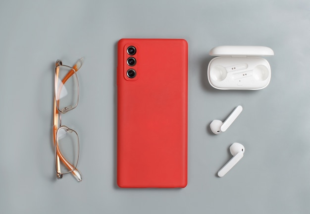 Smartphone, glasses and white wireless earphones with a case top view on grey background