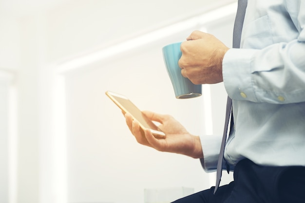 Smartphone in hand of businessman during coffee-break checking email
