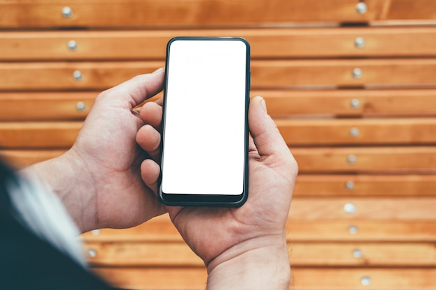 Smartphone in the hands of a man, against the background of a wooden bench.