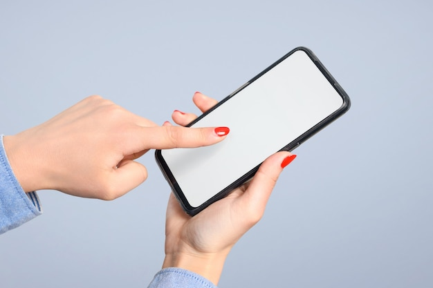 Smartphone in the hands of a woman, on a blue background. touches the touchscreen with his finger.