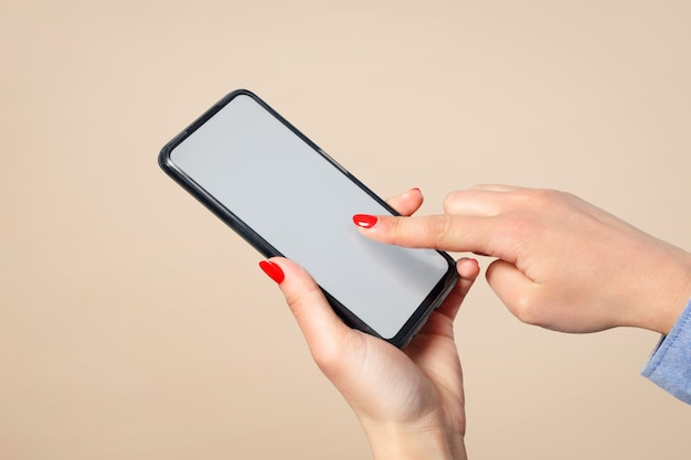 Smartphone in the hands of a woman, on a cream background. touches the touchscreen with his finger.