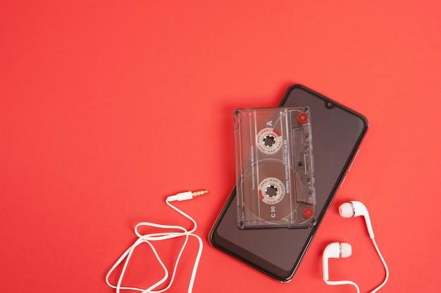 赤い背景のスマートフォンのヘッドフォンとオーディオカセット、思い出のコンセプト、現代の技術と過去の技術