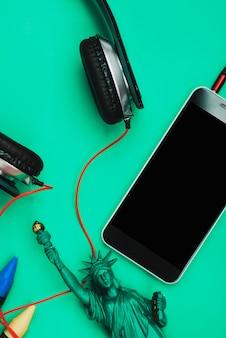 Смартфон, наушники и миниатюрная статуя свободы