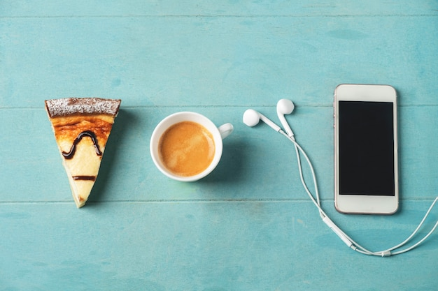 Smartphone, headphones, coffee cup and cheesecake