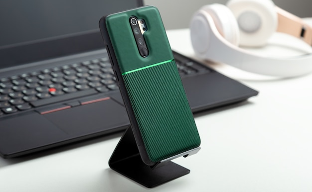 Smartphone on holder in protective case on smartphone back near black laptop on modern white work space. white table in home or office with phone laptop headphones. long web banner.