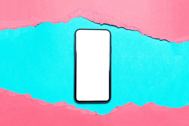Smartphone in hole of torn pink paper on cyan color.