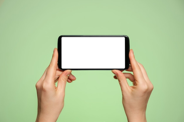 Smartphone horizontally with a blank screen in a woman's hand.