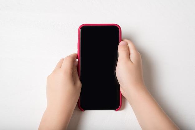 밝은 표면에 어린이 손에있는 스마트 폰