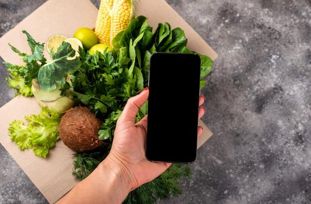 女性の手と新鮮な有機野菜のフルボックスのスマートフォン。