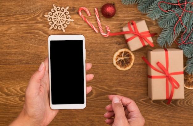 Смартфон в женской руке над рождественскими украшениями. приложение для покупок в интернете