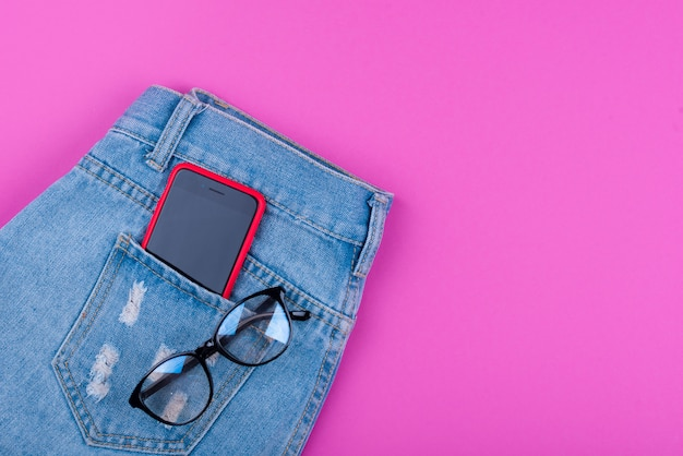 Смартфон в переднем кармане джинсов с очками и монетами алжира