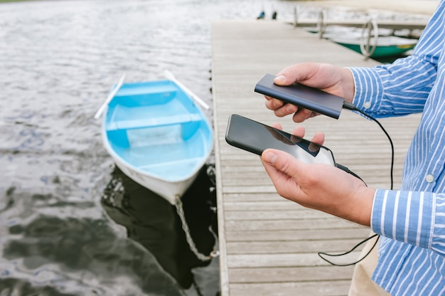 손에 스마트폰 전원 은행에서 충전하는 남자. 물과 부두에 보트의 배경. 여행을 주제로 한 개념입니다.