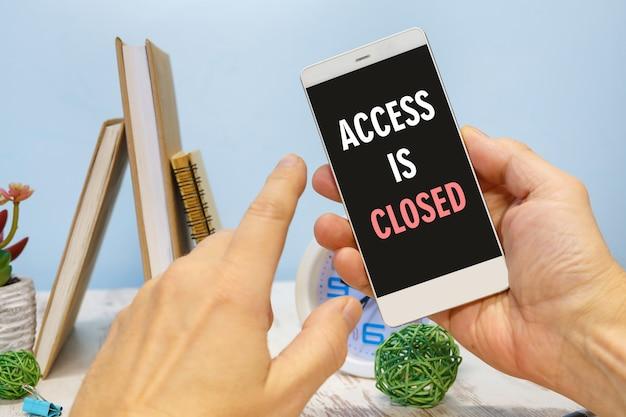 Смартфон в руке с надписью доступ закрыт рядом с канцелярскими товарами