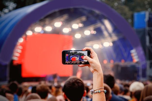 Смартфон в руках на музыкальном шоу.