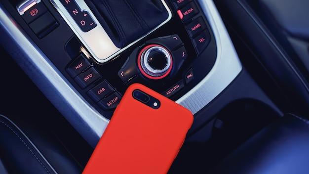 Смартфон в красном корпусе с двойной камерой в салоне современного роскошного автомобиля