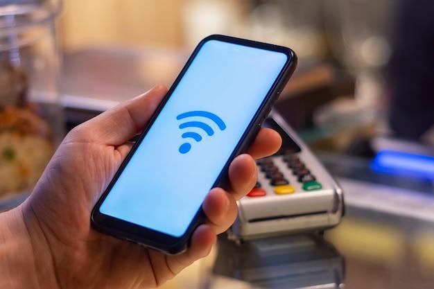 決済端末を背景にnfc技術を使用した店内のスマートフォン。