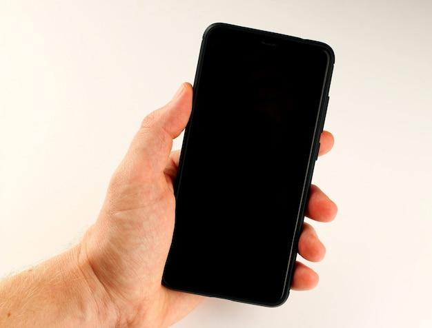 白い表面の手にスマートフォンをクローズアップ
