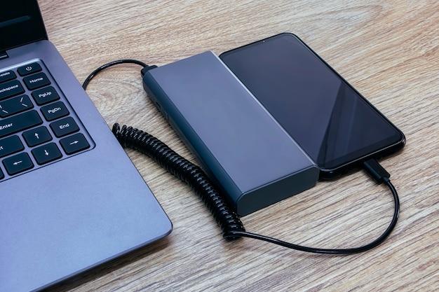 Смартфон заряжается от пауэрбанка. портативное зарядное устройство с ноутбуком на деревянном столе.