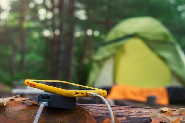 Смартфон заряжается с помощью портативного зарядного устройства. power bank заряжает телефон на улице с рюкзаком на фоне палатки.