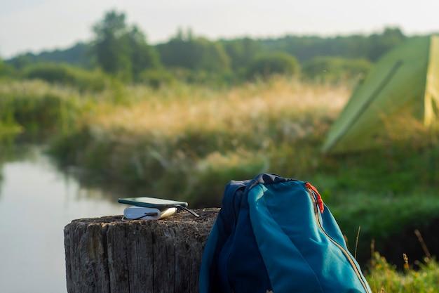 スマートフォンは携帯用充電器で充電します。パワーバンクは、テントを背景にバックパックを背負って屋外で携帯電話を充電します。