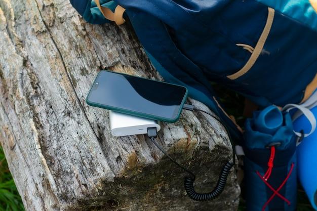 스마트폰은 휴대용 충전기를 사용하여 충전됩니다. power bank는 자연 관광을 위해 배낭을 메고 야외에서 전화를 충전합니다.