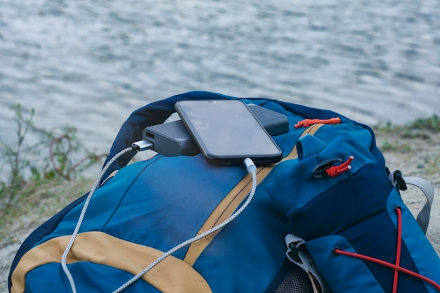 스마트폰은 휴대용 충전기를 사용하여 충전됩니다. power bank는 자연과 강을 배경으로 관광을 위해 배낭을 메고 야외에서 전화를 충전합니다.