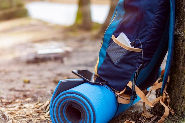Смартфон заряжается с помощью портативного зарядного устройства. power bank заряжает телефон на природе с рюкзаком для туризма на фоне природы и реки.