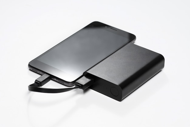 Smartphone is charging from the black battery power bank