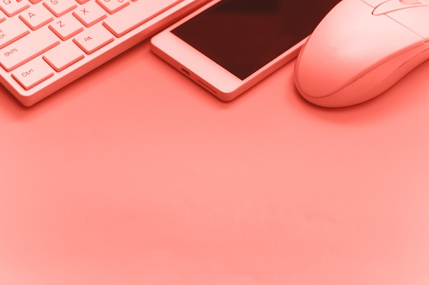 Smartphone,keyboard,mouse on pink backgroundcopy space toned