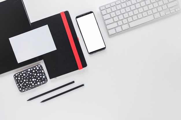 Smartphone and keyboard near stationery on white table
