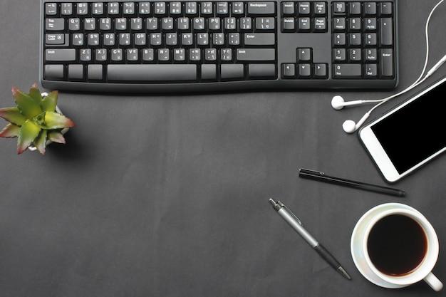 검은 책상에 스마트 폰, 키보드, 노트북, 커피 컵, 펜 및 용품 장소.