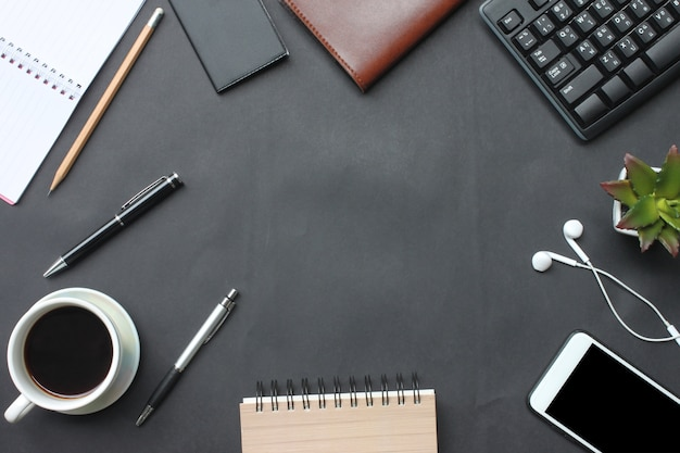 Smartphone, keyboard, notebook, coffee cup, pen and supplies place on a black desk.
