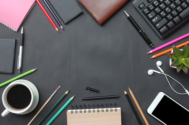 Smartphone, keyboard, notebook, coffee cup, pen and supplies place on a black desk in the