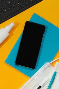 オレンジ色のテーブルにスマートフォンのキーボードの文房具と手指消毒剤