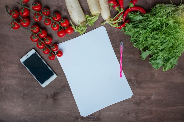 Smartphone on the kitchen table on a background of fresh vegetables. food background. place for text. background menu table. healthy balance food.