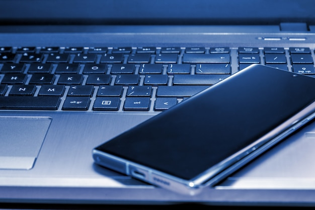 Smartphone on a laptop. laptop keyboard and a touchpad. business concept. web concept