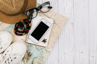 Smartphone lies on a notebook beforeon the map, hat, keds and glasses around it